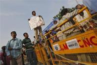 A protester holds a placard as he stands on top of a police barricade during a protest in New Delhi
